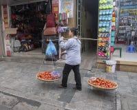 Vietnamese straatventer in Hanoi, met bamboekader over schouder die twee grote manden van tomaten voor verkoop dragen stock foto