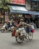 Vietnamese straatventer in Hanoi, op fiets dragende goederen voor verkoop stock afbeeldingen