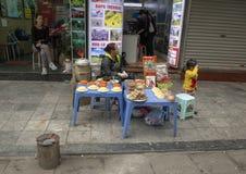 Vietnamese straatventer in Hanoi, verkopend voedsel van plastic stoeplijsten stock afbeelding