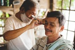 Vietnamese street barber shave. A Vietnamese street barber shaving a man using an old fashion straight razor blade while wearing a mask Stock Image