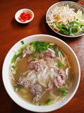 Vietnamese street food beef noodles. A photograph of a dish popular on the streets of Vietnam - Pho tai beef and white rice noodles soup with fresh mint leaves stock photography