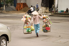 Vietnamese Street Vendor. A Vietnamese street vendor in Ho Chi Minh City (Saigon) carrying their goods across a street royalty free stock photography