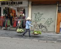 Vietnamese street vendor in Hanoi, with bamboo frame over shoulder carrying two big baskets of vegetables for sale. Pictured is Vietnamese street vendor in Hanoi royalty free stock images