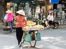 Vietnamese street vendors act and sell their vegetables and fruit products in Hanoi, Vietnam royalty free stock photo