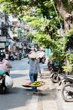Vietnamese street vendors act and sell their vegetables and fruit products in Hanoi, Vietnam royalty free stock image