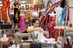 Vietnamese tailor woman sews traditional silk dress Royalty Free Stock Image