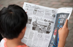 Vietnamese teenager reads newspaper Royalty Free Stock Photos