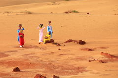 Vietnamese in traditional Ao Dai gathering at sand dunes. Vietnamese women in colourful traditional dress with basket at their head gathering at red sand dunes Stock Image