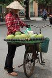 Vietnamese vendor. Hanoi, Vietnam - July 13, 2014: Vietnamese vendor cycling her mobile stall on a street of Hanoi capital. Many Vietnamese earn their living as Royalty Free Stock Images