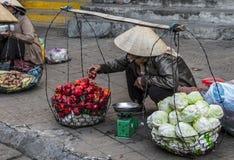 Vietnamese verkopers die fruit en groenten verkopen Stock Afbeelding