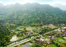 Vietnamese village among rice fields. Ninh Binh, V. Amazing panorama view of Vietnamese village among rice fields and limestone rocks at the early morning. Ninh Royalty Free Stock Photo