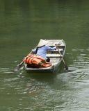 Vietnamese vrouw die met kegelhoed haar boot paddelen Royalty-vrije Stock Foto's