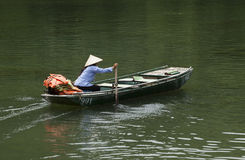 Vietnamese vrouw die met kegelhoed haar boot paddelen Stock Foto