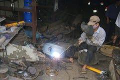 Vietnamese welder on the sidewalk stock photography