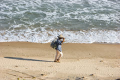 Vietnamese woman on the beach. Vietnamese woman walking on the beach and carries  a fishing net. Vietnam. Phan  Thiet Royalty Free Stock Image