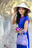 Vietnamese woman in blue Ao Dai holding flowers Stock Photography