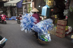 Vietnamese woman carries old plastic bottles Stock Photo