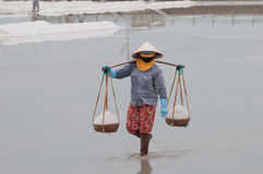 Vietnamese woman carrying baskets with salt. Vietnamese woman carrying hard baskets full of salt at salt-lake in Vietnam Stock Image