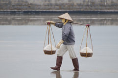 Vietnamese woman carrying baskets with salt. Hard work of Vietnamese women at salt-lakes in Vietnam Royalty Free Stock Image