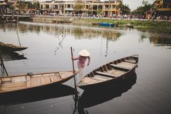 Vietnamese woman crossing canoes. A Vietnamese woman crosses over from one canoe boat to another wearing an Asian conical hat that hides her face Stock Photo