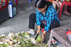 A Vietnamese woman is cutting coconut for travellers on a treet vendor Stock Photos