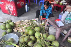 A Vietnamese woman is cutting coconut for travellers on a treet vendor Royalty Free Stock Photos