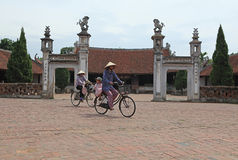 Vietnamese woman cycling on a country road Royalty Free Stock Photo