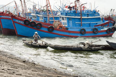 Vietnamese woman paddling alongside large fishing boats stock images