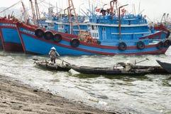 Vietnamese woman paddling alongside large fishing boats Stock Images