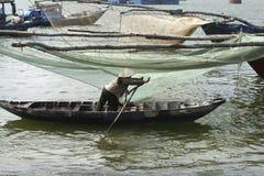 Vietnamese woman paddling alongside Large Fishing Nets At The Fishing Village in Da Nang, South Vietn Stock Photography