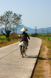 Vietnamese woman riding bicycle Stock Image