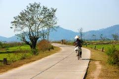 Vietnamese woman riding bicycle. BUON ME THUOT, VIET NAM- FEB 7: Vietnamese woman riding bicycle on country road, beautiful of natural landscape at Daklak Stock Photography