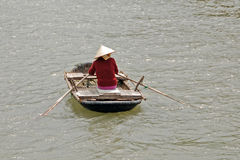 Vietnamese woman rowing. Vietnamese woman in a hat seen rowing in ha long bay royalty free stock photo