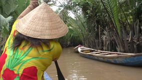 Vietnamese woman rows a boat, Mekong River. Vietnamese woman rows a boat in Mekong River in Vietnam stock footage