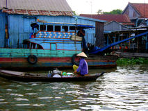 Vietnamese woman selling food on the Mekong delta. Floating village on the Mekong delta river in the background. Woman wearing purple with a straw hat ready to stock photo