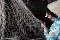 Vietnamese woman sewing fishing net Stock Image