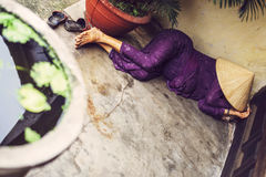 A Vietnamese woman takes an afternoon nap under the popular coni Royalty Free Stock Photos