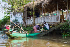 Vietnamese Woman trade fruit and vegetables from a wood boat Royalty Free Stock Photos