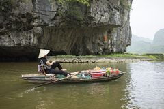 Vietnamese woman in traditional conical hat rows boat into natural cave on Ngo Dong river, Tam Coc, Ninh Binh, Vietnam Royalty Free Stock Photo