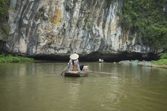 Vietnamese woman in traditional conical hat rows boat into natural cave on Ngo river, Tam Coc, Ninh Binh, Vietnam Royalty Free Stock Photography