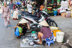 Vietnamese woman in traditional conical hat is selling fish Royalty Free Stock Images