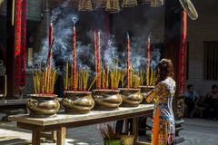 Vietnamese woman in traditional dress ao dai praying with incense stick in the burning pot of the Chinese pagoda in Ho Chi Minh. Vietnamese woman in traditional Royalty Free Stock Image