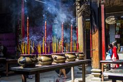 Vietnamese woman in traditional dress ao dai praying with incense stick in the burning pot of the Chinese pagoda in Ho Chi Minh. Vietnamese woman in traditional Stock Photo