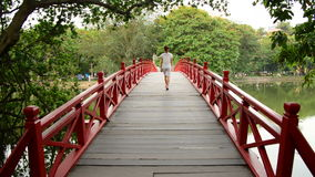 Vietnamese Woman Walking over The Huc Bridge on Hoan Kiem Lake in Hanoi Vietnam stock video
