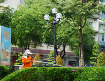 Vietnamese woman watering flowers at a park Royalty Free Stock Images
