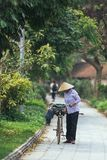 Vietnamese woman wearing conical hat walking with her bicycle on the way in summer near Trang An Grottoes in Ninh Binh, Vietnam royalty free stock photography