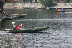 Vietnamese woman wearing purple long arm t-shirt conical hat rowing boat by her feet on the river at Trang An Grottoes. Vietnamese woman wearing purple long arm Royalty Free Stock Photo