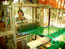 Vietnamese woman weaving in village. Woman using a weaving machine made from wood to make green material stock image