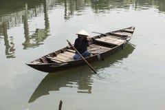 Vietnamese woman on wooden boat. Hoian Vietnam. Vietnamese woman sitting on a wooden boat. Hoian, Vietnam Stock Image