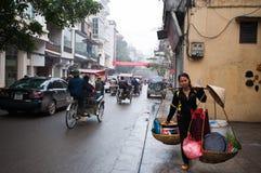 Vietnamese women. HANOI, VIETNAM - March 4: An unidentified road side peddler sells food in Hanoi, Vietnam on March 4,2012 Stock Images
